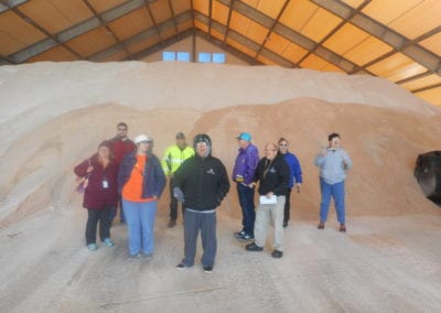 clients in front of a sand pile